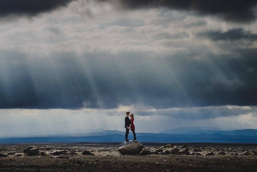 Paar seisab kivi peal Islandil päikesekiired paistmas läbi pilvede kihlumispildid pulmapildid pulmafotograaf Mait Jüriado