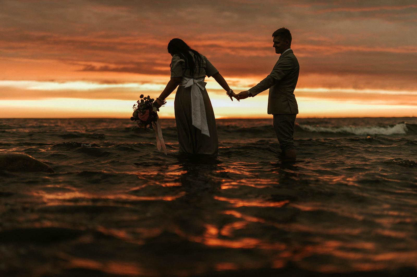 Pruutpaar seisab meres Lahemaa rahvuspark pulmafotograaf