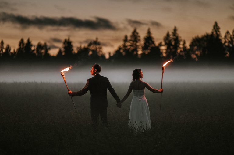 Bride and groom holding torches on a misty field in the evening in Estonia