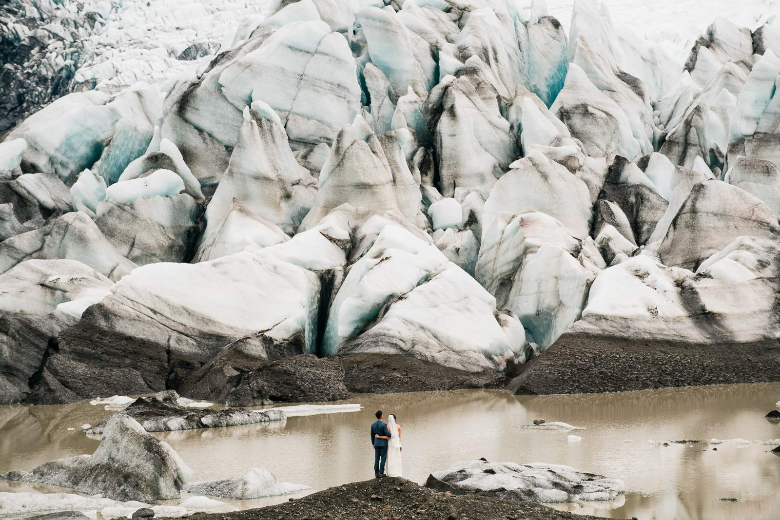 Bride and groom standing in front of blue glacier in Iceland