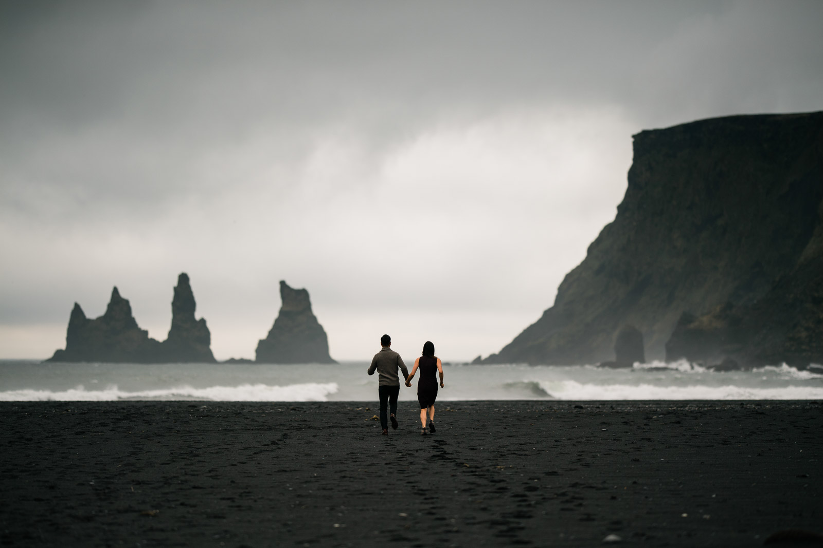 Bride and Groom running on black sand beach rock formations standing out from the sea in Iceland