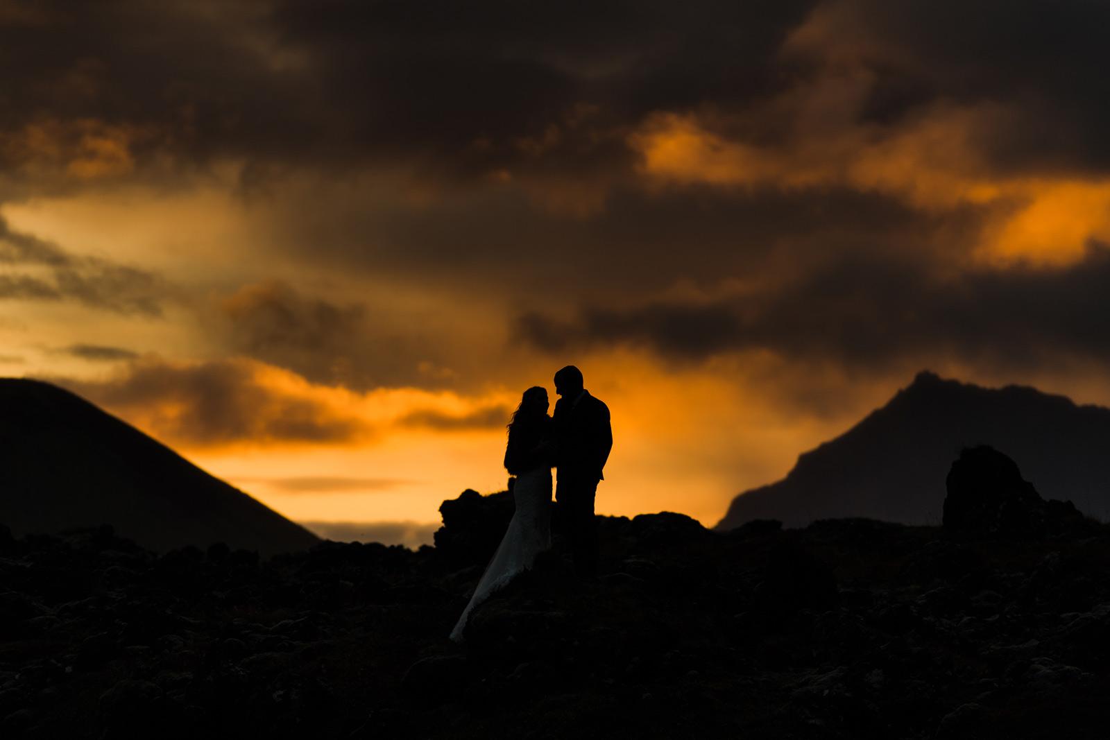 Pruut ja peigmees seismas päikseloojangul Islandil