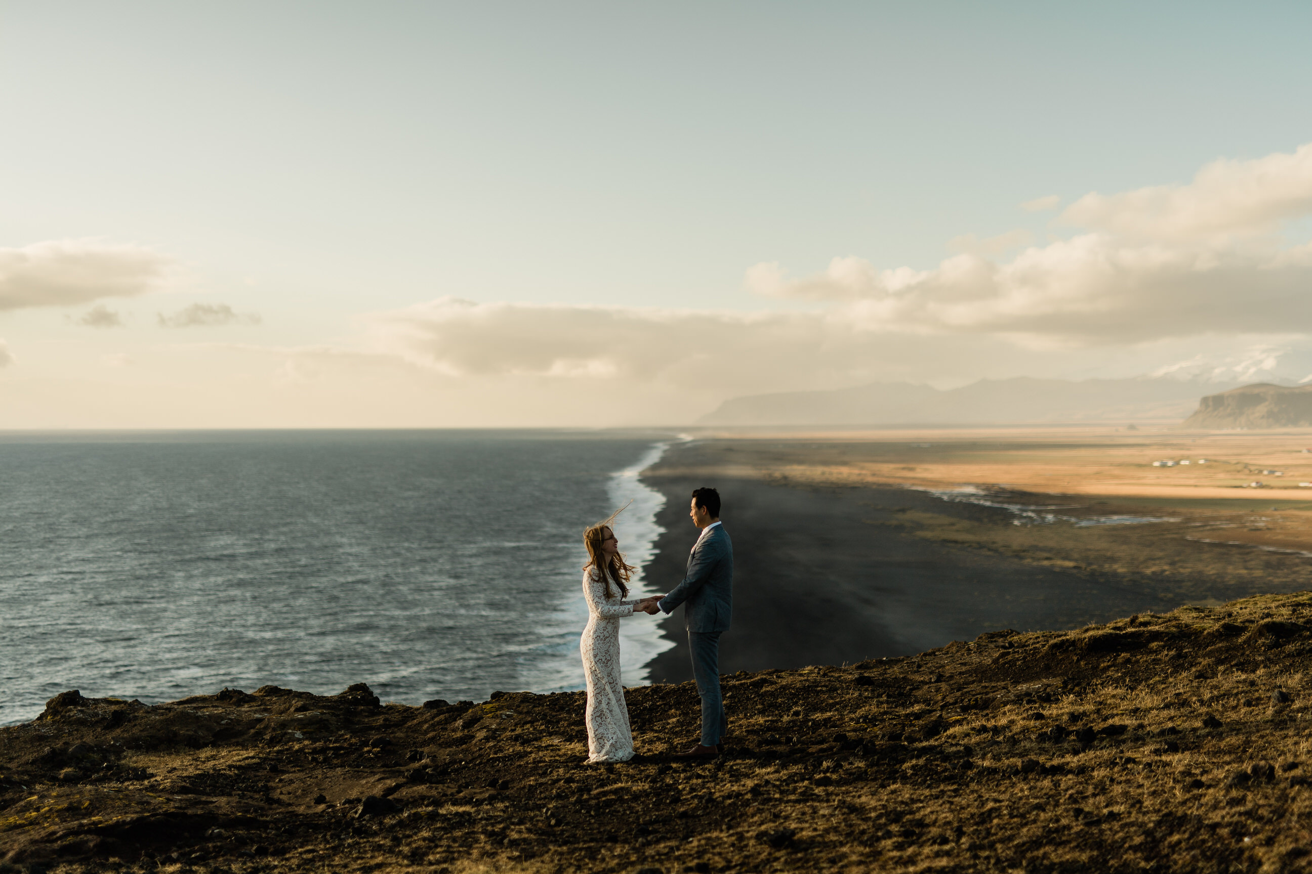 Bride and groom standing on top of the hill in Iceland the ocean behind