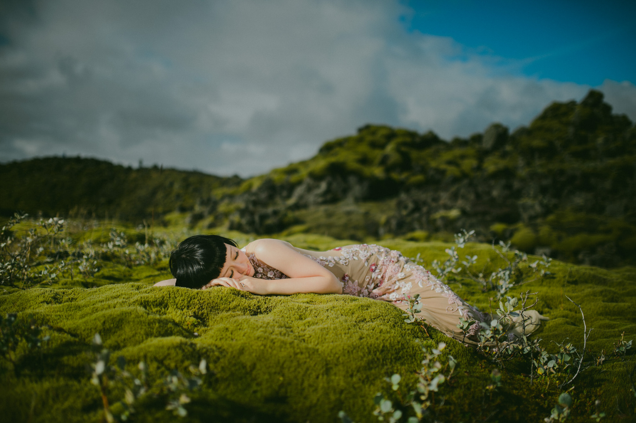 Fairytale bride sleeping on green moss on a sunny day in Iceland