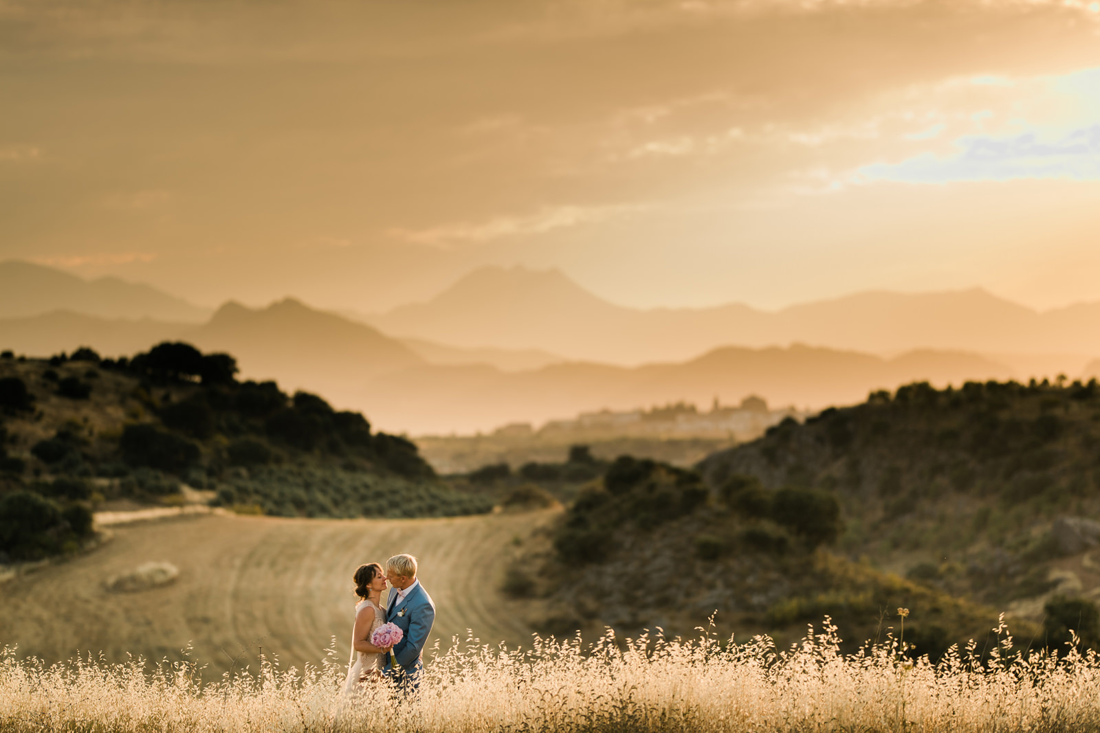 Bride and Groom on a Spanish cornfield mountains behind during golden hour near Ronda
