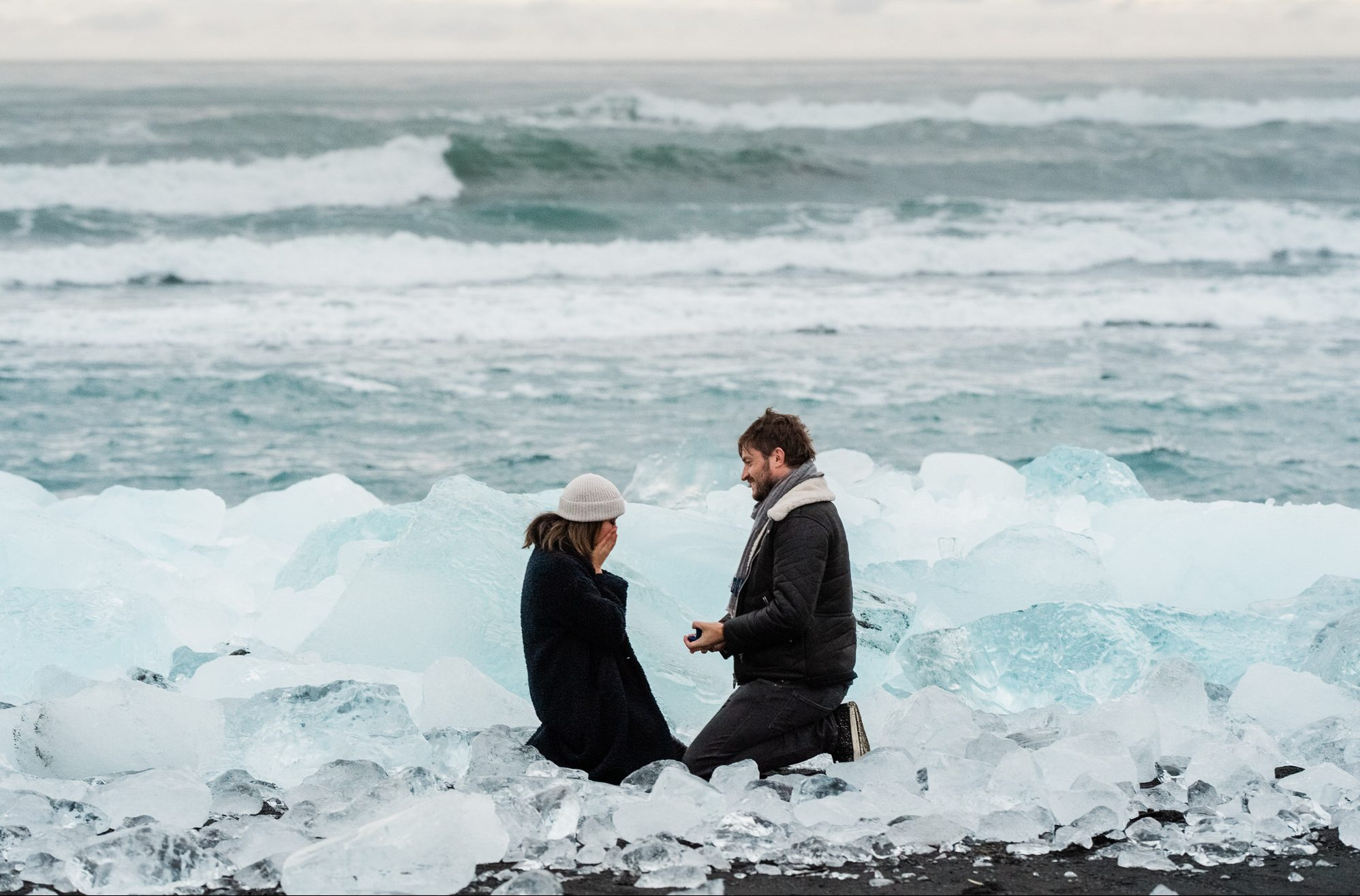 Man proposing his girlfriend between the Icebergs during the sunrise in Ice Lagoon Jokulsarlon in Iceland