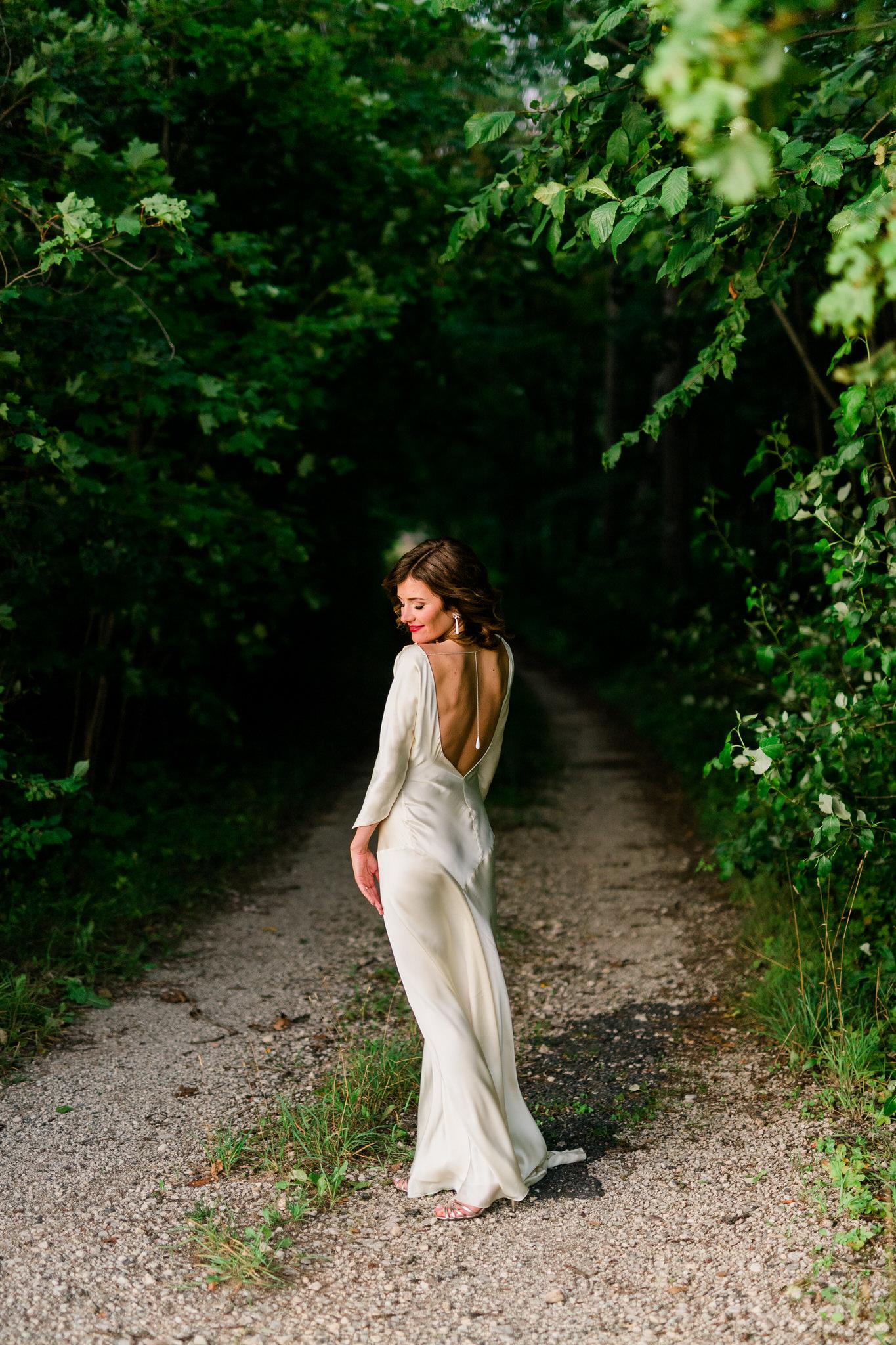 Bride in a white silk dress standing on gravel road near Kau Manor in Estonia