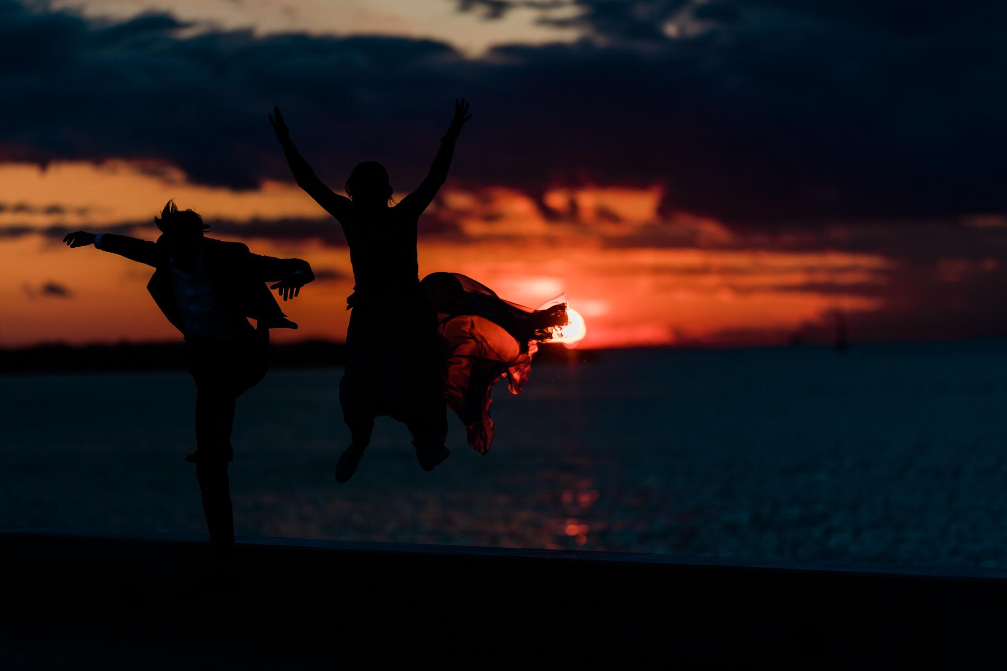 Pruutpaar Tallinnas istub päikeseloojangu ajal mere ääres