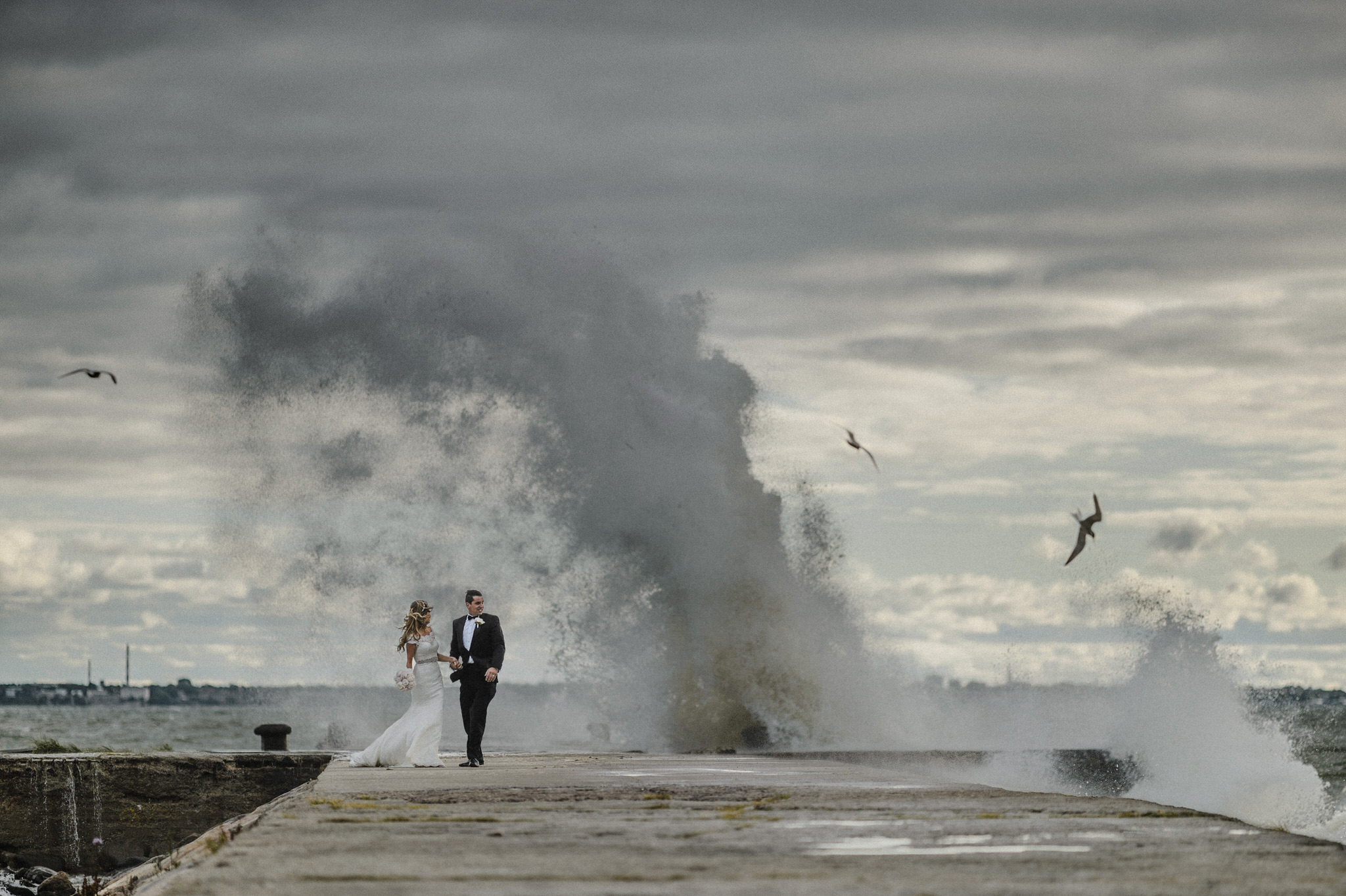 Huge wave crashing over bride and grooms head at the seaside