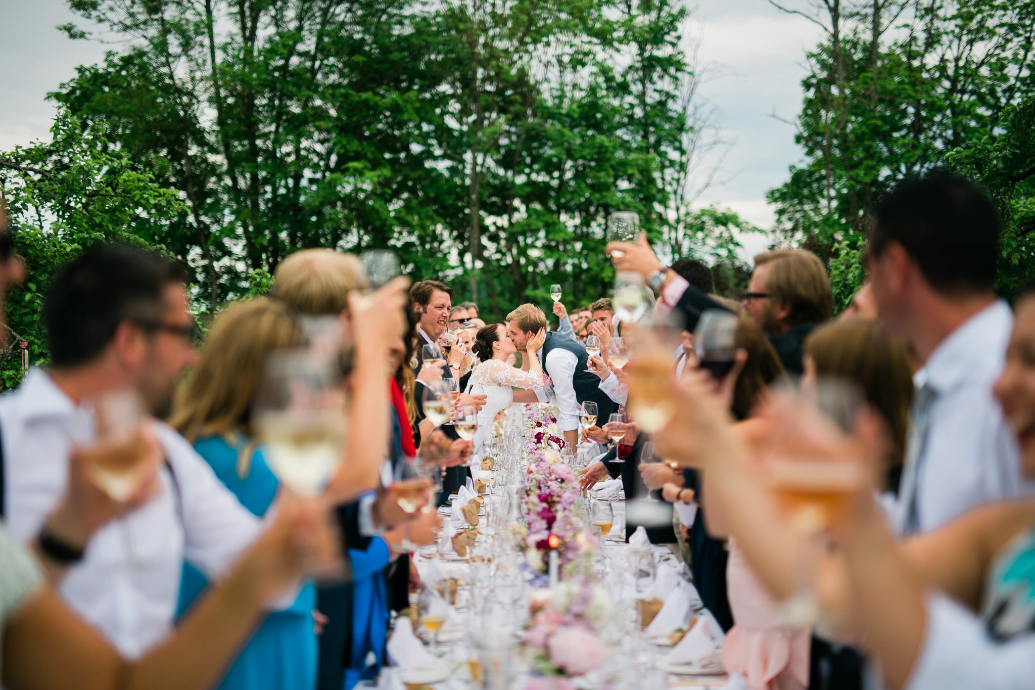 Bride and groom kissing dinner table wedding guests around