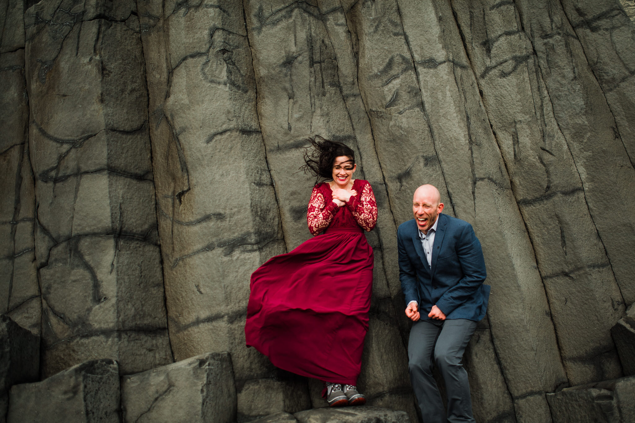 Bride and groom on basalt colums very heavy wind in Iceland