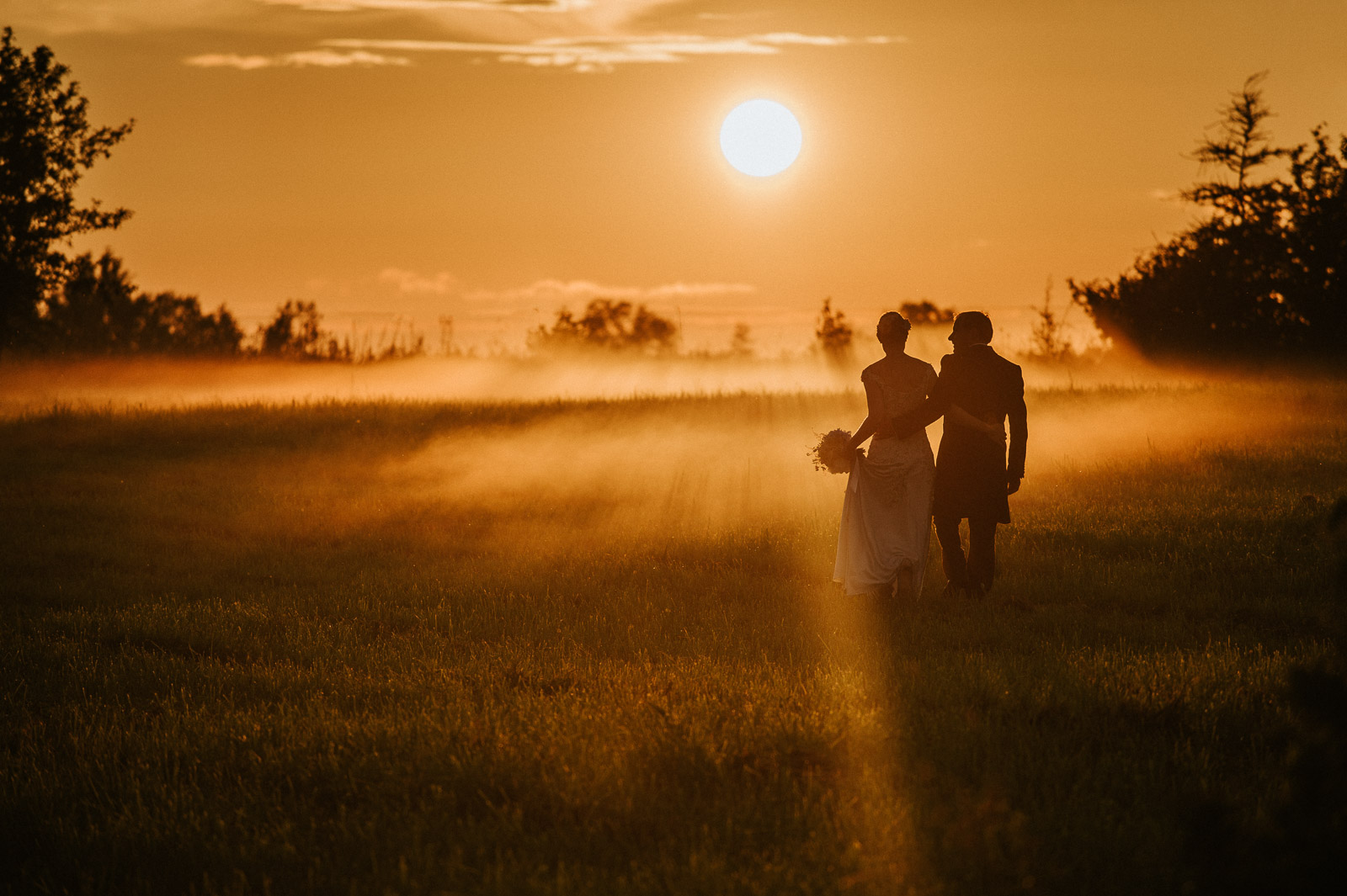 Bride and groom walking on a foggy field towards the sunset