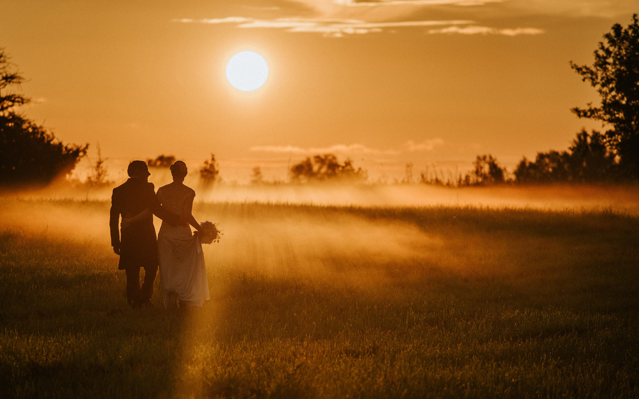 Bride and Groom walking on foggy field Mait Juriado MJ Studios